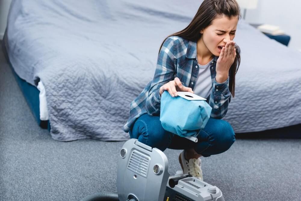 Kurz domowy a zdrowie - pani kaszle nad workiem z odkurzacza